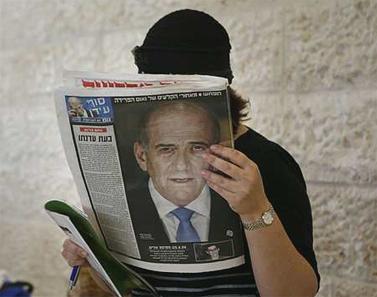 קוראת בעיתון על התפטרותו של ראש הממשלה אהוד אולמרט, 31 ביולי 2008 (צילום: מיכל פתאל)