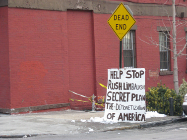 """שלט מחאה. הכיתוב: """"עזרו לעצור את התוכנית הסודית של ראש לימבו לדה-מונטיזציה של אמריקה"""". ברוקלין, ניו-יורק (צילום: טריטופ-מאם, רשיון CC)"""