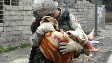 """קצין אמריקאי מחלץ ילדה עיראקית שנפצעה בפיצוץ מכונית תופת. הסיפור מאחורי התמונה מתואר בשיגור """"ילדה קטנה"""" (צילום: מייקל יון, 2005)"""