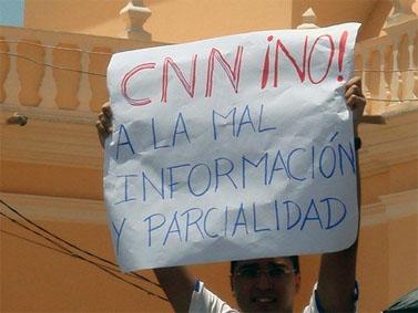 מפגין נגד סלאיה מניף כרזה נגד ההטיה של התקשורת המערבית בסיקור הנעשה בהונדורס (צילום: giggy, רישיון cc-by-nc)