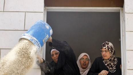 פלסטינית שופכת פסולת בניין על שוטרים, ראס אל-עמוד, 9.10.09(צילום: מתניה טאוסיג)