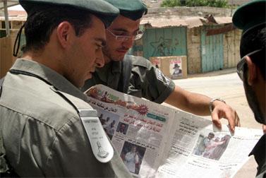 """חיילי מג""""ב מעיינים בעיתון """"אל-קודס"""", חברון, מאי 2006 (צילום: פלאש 90)"""