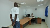 פליט סודאני ושוטר במחנה המעצר בקציעות, 3.8.09 (צילום: משה שי)