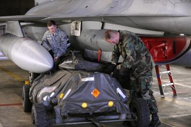 חייל אמריקאי מטעין פצצה על מטוס F-16, לקראת תקיפה בלוב (צילום: U.S. Air Force, רשיון cc-by-nc 2.0)