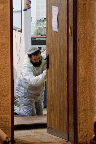"""איש זק""""א בוחן את בית משפחת פוגל באיתמר לאחר טבח המשפחה (צילום: אורן נחשון)"""