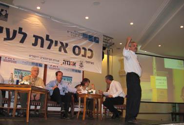 """יוסי בר-מוחא (מימין) על במת כנס אילת לעיתונות (צילום: """"העין השביעית"""")"""