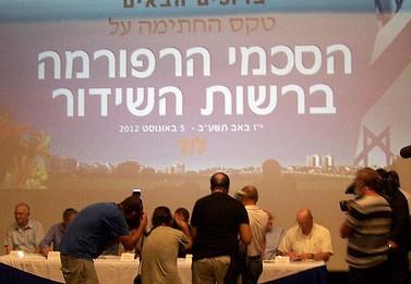 """צלמים מתעדים את הנהלת רשות השידור בטקס החתימה על הרפורמה בהיכל התרבות בלוד, 5.8.12 (צילום: """"העין השביעית"""")"""