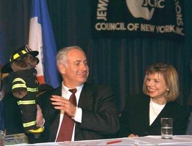 """ראש הממשלה בנימין נתניהו, מלווה ברעייתו שרה, מציג דב צעצוע שקיבל במתנה לילדיו בכנס ה-JCRC בניו-יורק. 11.7.96 (צילום: יעקב סער, לע""""מ)"""