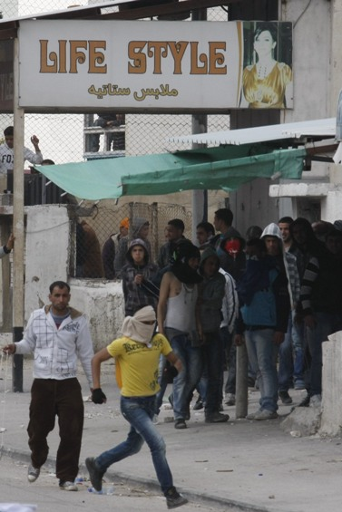 פלסטינים משליכים אבנים לעבר כוחות הביטחון הישראליים במחסום קלנדיה, שלשום (צילום: אורן נחשון)