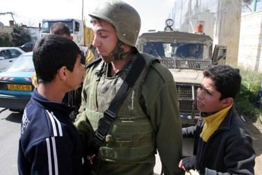 """חייל צה""""ל ומפגין פלסטיני, אתמול בחברון (צילום: נאג'ה השלמון)"""