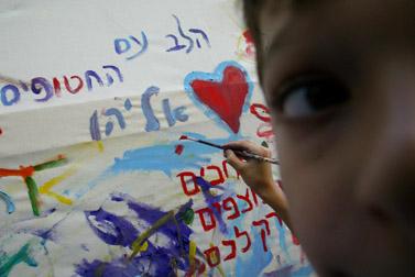 מציירים גרפיטי באירוע למען שחרור החטופים (צילום: אוליביה פיטוסי)