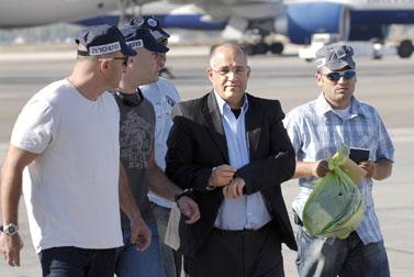 בועז יונה מובל על-ידי שוטרים עם נחיתתו בארץ (צילום: ניר כפרי)