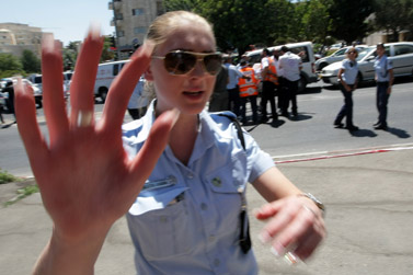 שוטרת עוצרת מלצלם בזירת הפיגוע, אתמול בירושלים (צילום: קובי גדעון)