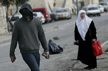 """צעיר פלסטיני שורף דגל במזרח ירושלים ואחר מיידה אבנים, כחלק מגל הפגנות בגדה המערבית ב-2 בינואר, שעליו הכריז חמאס כ""""יום הזעם"""" (צילום: אוליביה פיטוסי)"""