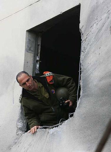 """קצין צה""""ל בוחן בית שנפגע מרקטת גראד, היום באשקלון (צילום: צפריר אביוב)"""