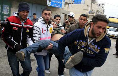 """פלסטיני פצוע מאש צה""""ל בעת הפגנה נגד המבצע בעזה, 23 בינואר, קלנדיה (צילום: עיסאם רימאווי)"""