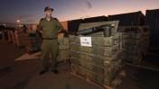 """חייל צה""""ל שומר על תיבות נשק שנתפס בלב ים, אתמול בנמל אשדוד (צילום: צפריר אביוב)"""