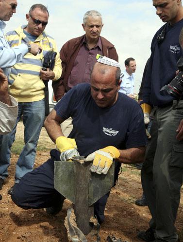 נחום ברנע (שני מימין) ושמעון שיפר (שלישי מימין) בוחנים אתר נפילת קסאם בשדרות (צילום: יוסי זמיר)