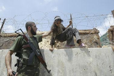 פעיל חמאס וילדה פלסטינית על הגבול הדרומי של רצועת עזה (צילום: עבד אל-רחים כתיב)