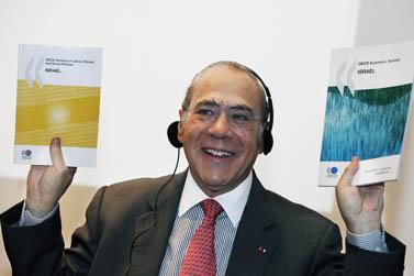 """אנחל גוריה, מזכ""""ל ה-OECD, מניף את הדו""""ח על ישראל שחיבר הארגון, בסמינר של בנק ישראל אתמול בירושלים (צילום: מרים אלסטר)"""