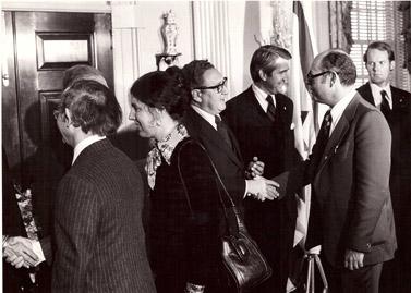 """גולדשטיין (שני מימין) לוחץ את ידו של מזכיר המדינה האמריקאי הנרי קיסינג'ר בבית-הלבן בוושינגטון, 1976 (צילום: לע""""מ)"""