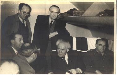 אורי קיסרי (עומד במרכז) עם ראש הממשלה דוד בן-גוריון במטוס בשנות ה-50. ליד החלון: נחמיה ארגוב, השליש הצבאי. קיצוני משמאל: אברהם גלבוע, קונסול ישראל בפריז