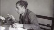 """נתן אלתרמן ליד שולחן הכתיבה במערכת """"הארץ"""" (אוסף מרדכי נאור)"""