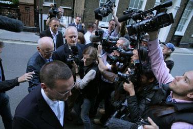 צלמים ועיתונאים מקיפים את ג'יימס מרדוק (משמאל בקדמת התמונה) ואת אביו, רופרט מרדוק (מאחוריו), עם הגיעו של האחרון ללונדון בתחילת השבוע (צילום: ג'ד גובל, רישיון cc)