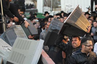 חסידיו של אמנון יצחק משליכים מכשירי טלוויזיה לאשפה במחאה נגד התקשורת הישראלית (צילום: נתי שוחט)