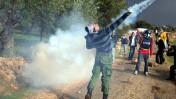 מפגין פלסטיני משליך רימון גז, שלשום במהלך ההפגנה ליד בילעין (צילום: עיסאם רימאווי)