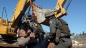 """שוטרי מג""""ב גוררים פלסטיני שניסה למנוע את בניית מחסום ההפרדה, שלשום (צילום: עיסאם רימאווי)"""
