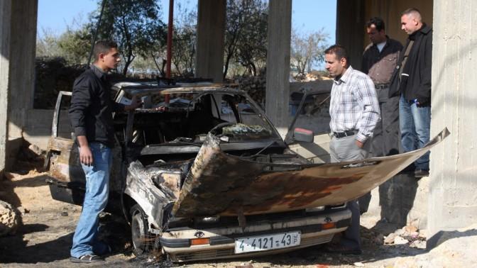 פלסטינים מתבוננים במכונית שהוצתה, אתמול בכפר ברוקין (צילום: עיסאם רימאווי)