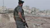 """חייל מג""""ב צופה מעיסאוויה אל עבר חומת ההפרדה, אתמול (צילום: יואב ארי דודקביץ')"""