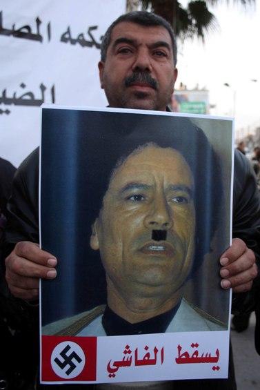 פלסטיני אוחז בכרזה בגנות מועמר קדאפי, השבוע ברמאללה (צילום: עיסאם רימאווי)