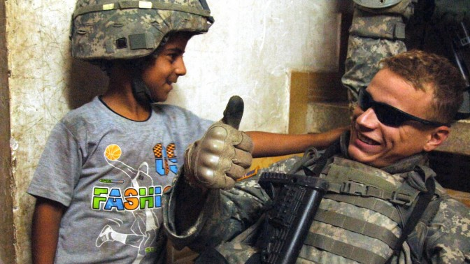 """חייל אמריקאי וילד עיראקי בבגדד, 29.11.07 (צילום: צבא ארה""""ב, לוק תורנברי, רשיון cc-by 2.0)"""