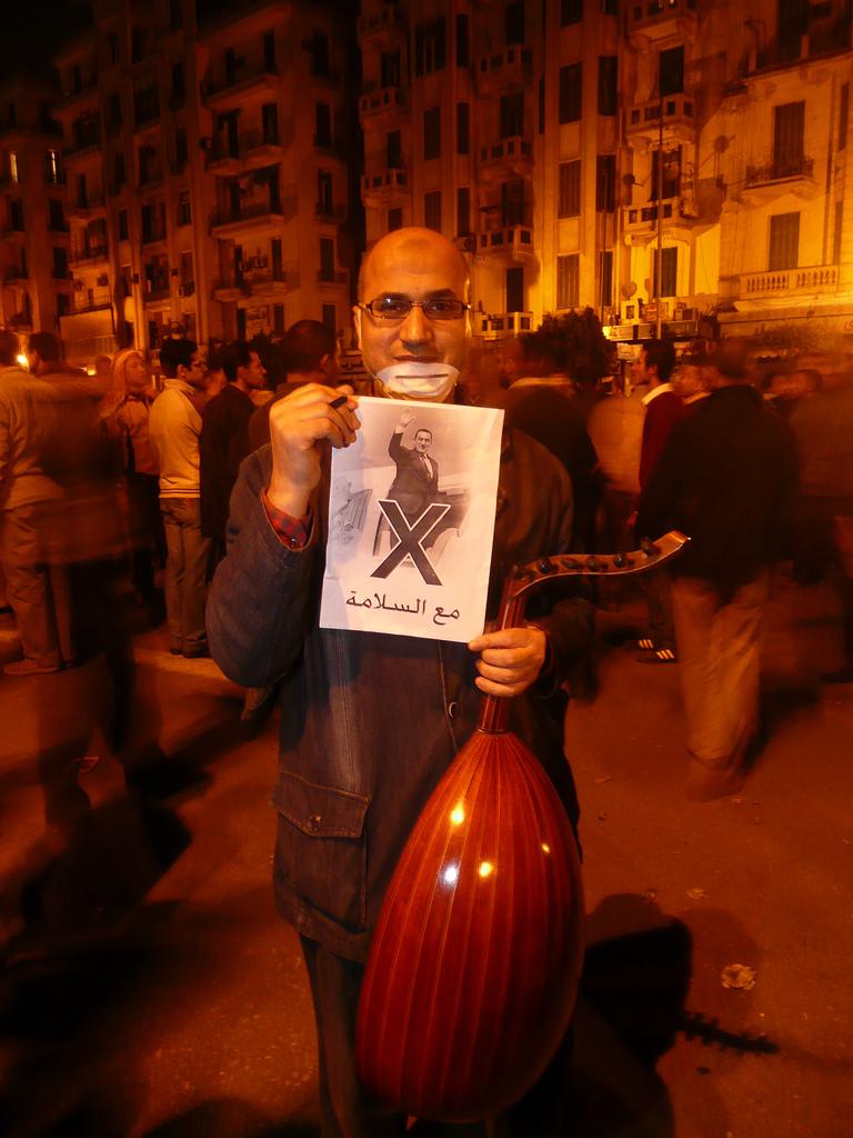 מפגין מצרי בכיכר תחריר נושא כרזה של הנשיא מובארכ נכנס למטוס (צילום: Al Jazeera English, רשיון cc-by-nd 2.0)