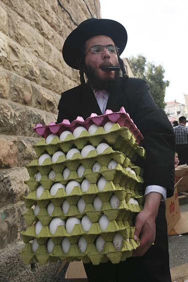 חסיד סאטמר מירושלים נושא מצרכים לעניים לפני הפסח (צילום: מתניה טאוסיג; פלאש 90)