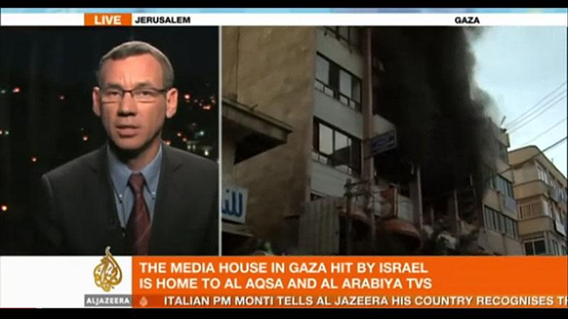 """מארק רגב, יועץ לעיתונות זרה במשרד ראש הממשלה, מתראיין באל-ג'זירה בנוגע להפצצת בניין ערוץ אל-אקצא בעזה במסגרת מבצע """"עמוד ענן"""" (צילום מסך)"""