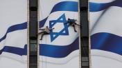 עובדים תולים דגל ישראל בכניסה לירושלים (צילום: יונתן זינדל)