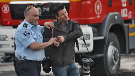 הצלם חגי אהרון מובל לניידת המשטרה, 10.4.13 (צילום: שי וקנין)