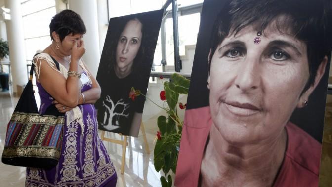 אשה מתייפחת כשהיא מביטה בתצלום של עצמה, בתערוכה במשכן הכנסת של נשים שהיו קורבנות של עבירות מין, 16.7.13 (צילום: מרים אלסטר)