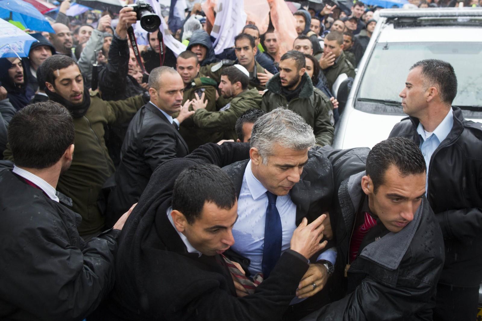 מאבטחי שר האוצר מניסים אותו ממפגינים מול משרד ראש הממשלה נגד רפורמת התעופה, 21.4.13 (צילום: יונתן זינדל)