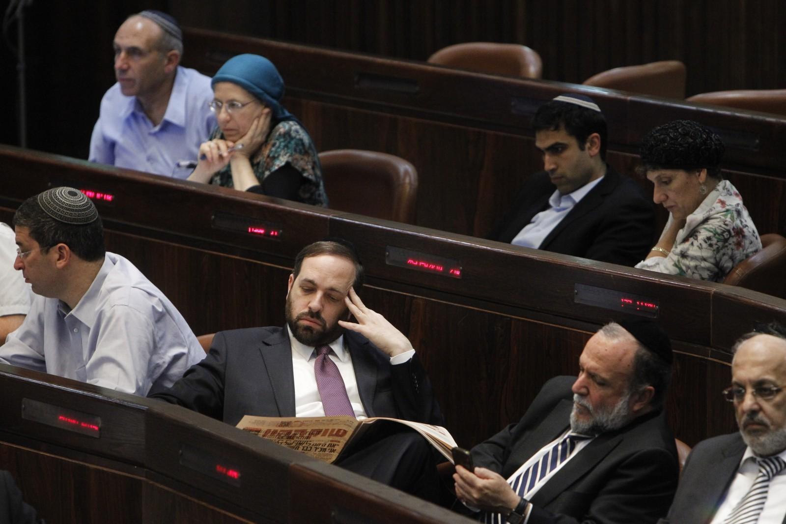 """חברי-כנסת של ש""""ס קוראים עיתון במליאת הכנסת, אתמול (צילום: מרים אלסטר)"""
