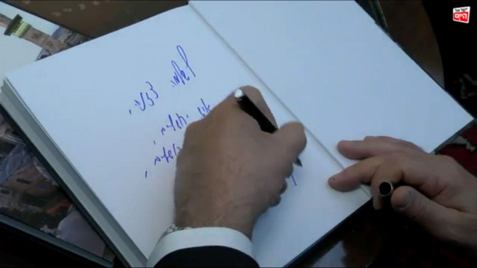 """ראש הממשלה בנימין נתניהו חותם על מדריך התיירות שכתב והעניק לו הכתב המדיני של """"ישראל היום"""", שלמה צזנה. מאי 2013 (צילום מסך, """"ישראל היום"""")"""