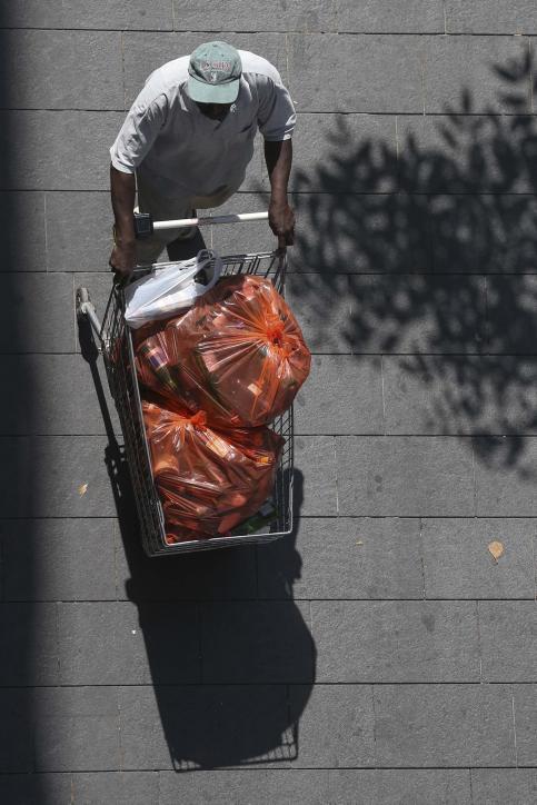 אדם דוחף עגלה מלאה בבקבוקים ריקים, אתמול בירושלים (צילום: פלאש 90)