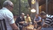 """ראש הממשלה מנחם בגין משחק שחמט עם יועץ נשיא ארה""""ב לבטחון לאומי זבגנייב בז'יז'ינסקי ברגע של מנוחה בשיחות השלום בין ישראל למצרים בקמפ דיויד, ארה""""ב. משמאל: מנהל לשכת רה""""מ יחיאל קדישאי. מביטים על המשחק אפרים פורן ושמחה דיניץ. ספטמבר 1978 (צילום: לע""""מ)"""