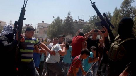 פלסטינים מציגים לראווה את כלי נשקם במהלך הלוויית הרוגי הפעולה הישראלית בקלנדיה, אתמול (צילום: עיסאם רימאווי)