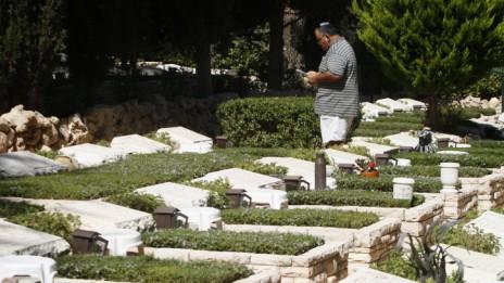אדם ניצב לצד קברו של חייל שנהרג במלחמת יום-כיפור. בית-העלמין הצבאי בהר הרצל (צילום: אורי לנץ)