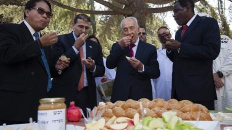 הנשיא שמעון פרס אוכל תפוח בדבש בחברת שגרירים זרים, 3.9.09 (צילום: פלאש 90)