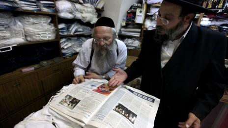 """יהודים חרדים מעיינים במהדורה האנגלית של """"המודיע"""". ירושלים, 7.9.11 (צילום: קובי גדעון)"""